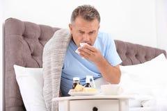 Manlidande från hosta och förkylning i säng arkivfoto