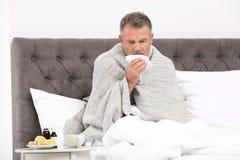 Manlidande från hosta och förkylning i säng royaltyfri fotografi