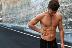 Manlidande från magen smärtar efter rinnande utomhus Sportskada arkivfoto