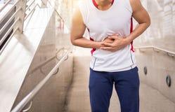 Manlidande från smärtar i skada för magekramper efter att ha joggat och genomkörare för sportövningsspring royaltyfri fotografi