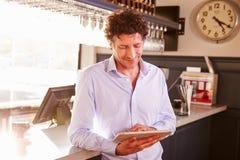 Manlig ägare för restaurangägare som använder den digitala minnestavlan fotografering för bildbyråer