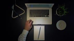 Manlig affärsman i den vita skjortan som sitter på tabellen i aftonen som arbetar på en bärbar dator och dricker kaffe overhead arkivfilmer
