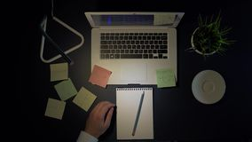 Manlig affärsman som sitter på tabellen i aftonen som arbetar på en bärbar dator och dricker kaffe Skjuten fast utgift lager videofilmer