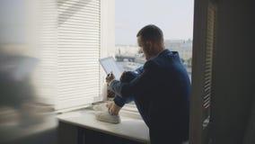 Manlig affärsman som studerar ekonomiskt bildsammanträde på fönsterbräda stock video