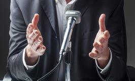 Manlig affärsman som talar till allmänheten på microen arkivbilder