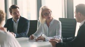 Manlig affärspartner för mogen kvinnlig ledarehandskakning över förhandlingtabellen