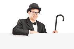 Manlig aktör som rymmer en rotting bak en panel Royaltyfri Bild