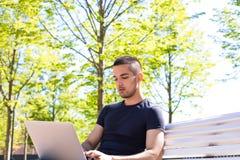 Manlig annonserande författare som skriver text för webbplats på netbook som utomhus sitter arkivbilder