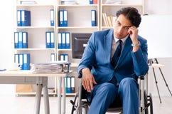 Manlig anställd i rullstolarbete på kontoret arkivbild