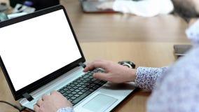 Manlig anställd som arbetar på bärbara datorn på kontorsskrivbordet, framkallande affärsprojekt Arkivfoton