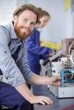 Manlig arbetare för stående som arbetar med fabriksutrustning arkivbild