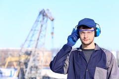 Manlig arbetare med hörlurar utomhus Royaltyfri Fotografi