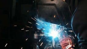 Manlig arbetare på en svetsningfabrik i en svetsningmaskering Svetsning på en industrianläggning stock video