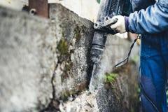 Manlig arbetare som använder det industriella konstruktionshjälpmedlet, den industriella tryckluftsborren med rivningskräp och ce Arkivbilder
