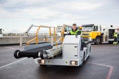 Manlig arbetare som kör bagagetransportörlastbilen på flygplatslandningsbana royaltyfri fotografi