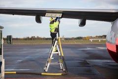 Manlig arbetare som tankar flygplanet, medan stå på momentstege arkivbilder