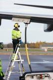 Manlig arbetare som tankar flygplanet, medan stå på stege royaltyfria foton
