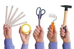 Manlig arbetares hand som rymmer olika hjälpmedel för hantverkhandel Royaltyfria Bilder