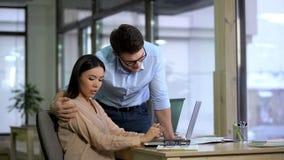 Manlig arbetsgivare som kramar den h?rliga kvinnliga deltagaren i utbildning, kvinna som chockas av mobbning arkivfoto