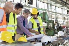 Manlig arbetsledare med arbetare som diskuterar över ritningar i bransch Fotografering för Bildbyråer