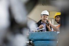 Manlig arbetsledare med undersökande metall för arbetare i bransch Royaltyfria Bilder
