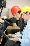 Manlig arbetsledare- och gaffeltruckchaufför Using Laptop Arkivbild