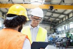 Manlig arbetsledare som diskuterar med den manuella arbetaren i metallbransch Arkivbild