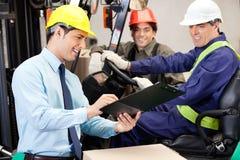 Manlig arbetsledare som meddelar med gaffeltruckchauffören Royaltyfria Bilder