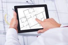 Manlig arkitekt som analyserar ritningen över den digitala minnestavlan Arkivfoto