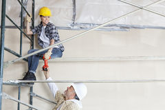 Manlig arkitekt som ger drillborren till den kvinnliga arbetaren på ställning på konstruktionsplatsen Royaltyfri Fotografi