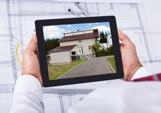 Manlig arkitekt som rymmer den digitala minnestavlan över ritning Royaltyfria Foton