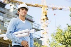Manlig arkitekt som rymmer hoprullade ritningar, medan stå på konstruktionsplatsen Fotografering för Bildbyråer