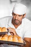 Manlig bagare Holding Baking Trays i bageri Royaltyfri Fotografi
