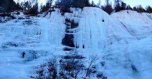 Manlig berghandbok som klättrar en brant fryst vattenfall på en kall vinterdag i fjällängarna royaltyfri fotografi