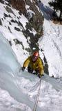 Manlig berghandbok som klättrar en brant fryst vattenfall på en kall vinterdag i fjällängarna royaltyfria foton