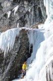 Manlig berghandbok som klättrar en brant fryst vattenfall på en kall vinterdag i fjällängarna arkivbild