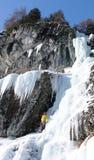 Manlig berghandbok som klättrar en brant fryst vattenfall på en kall vinterdag i fjällängarna royaltyfri bild