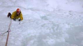 Manlig berghandbok som klättrar en brant fryst vattenfall på en kall vinterdag i fjällängarna royaltyfria bilder