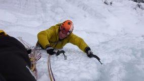 Manlig berghandbok som klättrar en brant fryst vattenfall på en kall vinterdag i fjällängarna arkivfoto