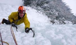 Manlig berghandbok som klättrar en brant fryst vattenfall på en kall vinterdag i fjällängarna royaltyfri foto