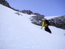 Manlig berghandbok som klättrar en brant snöcouloir på hans väg till en hög toppmöte i de schweiziska fjällängarna arkivbilder