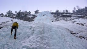 Manlig berghandbok som rappelling av en brant fryst vattenfall efter en isklättringutfärd Royaltyfria Bilder