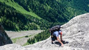 Manlig bergsbestigare på en brant och Rocky Mountain sida royaltyfria foton