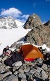 Manlig bergsbestigare som äter på basläger vid ett orange tält med ett spektakulärt berglandskap runt om honom arkivfoton