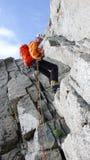 Manlig bergsbestigare som rappelling av en brant stenig kant i de franska fjällängarna nära Chamonix royaltyfria bilder
