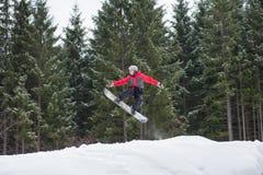 Manlig boarder på snowboarden som hoppar över lutningen Arkivfoto