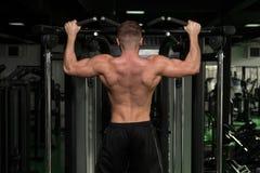 Manlig bodybuildingidrottsman nen Doing Pull Ups arkivbild