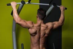 Manlig bodybuildingidrottsman nen Doing Pull Ups royaltyfri fotografi