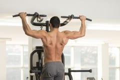 Manlig bodybuildingidrottsman nen Doing Pull Ups fotografering för bildbyråer