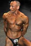 Manlig bodybuildingkonkurrent som visar hans bästa Arkivfoto